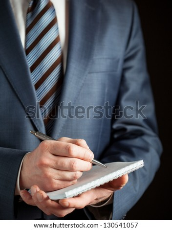 Businessman making notes on the paper, black background