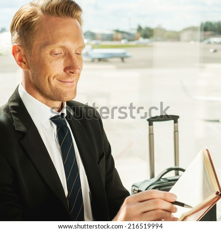 Businessman making notes. Side view of confident businessman in formalwear writing something in note pad while waiting for a flight in airport  - stock photo