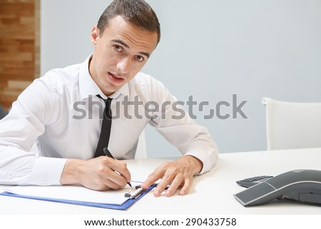 Businessman making notes while sitting at a desk in the office