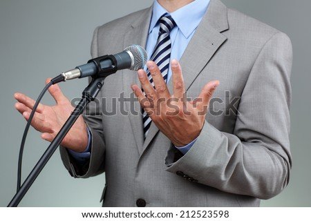 Businessman making speech with microphone and hand gesturing concept for explaining, protesting or belief - stock photo