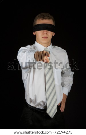 Businessman, male executive point finger with blindfold on his eyes isolated on black background, low key. - stock photo