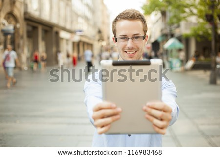 Businessman man hold tablet computer in public space - stock photo