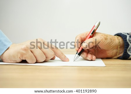 businessman man is pointing senior where to sign contract - stock photo