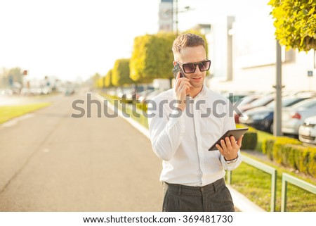 Businessman Man With Mobile Phone and Tablet computer in hands, In City, Urban Space - stock photo
