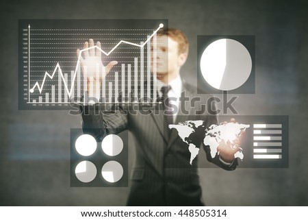 Businessman managing abstract business charts on concrete background - stock photo