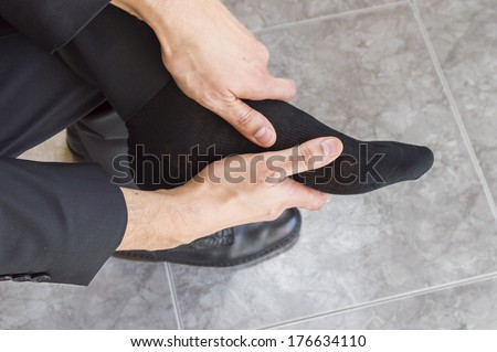 businessman massages tired feet and aching - stock photo