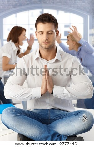 Businessman meditating at office with eyes closed sitting on desk, coworkers arguing in background. - stock photo