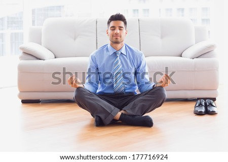 Businessman meditating in lotus pose on the floor in the office - stock photo