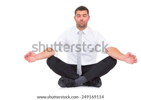 Businessman meditating in lotus pose on white background - stock photo