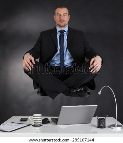 Businessman meditating in the office and in the air - stock photo