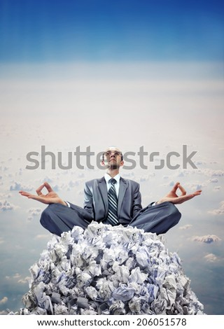 Businessman meditating on heap of documents - stock photo