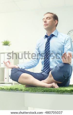 Businessman meditating on table in office