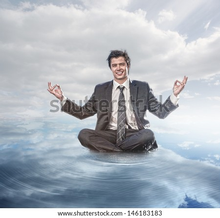 Businessman meditating on the water