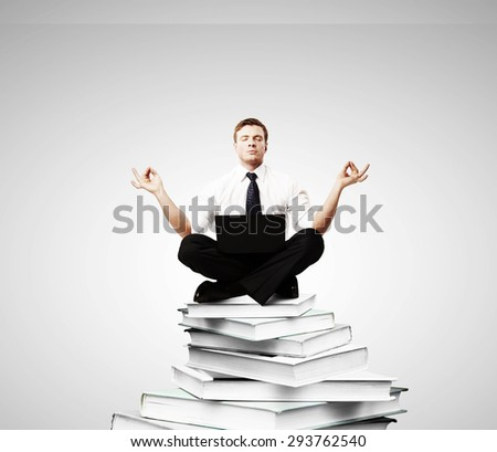 businessman meditation on a pile of books - stock photo