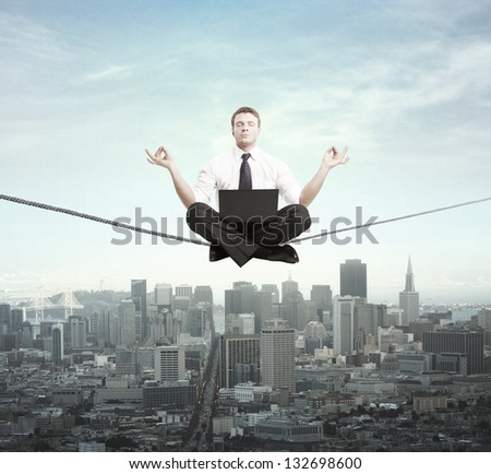 businessman meditation on rope and city