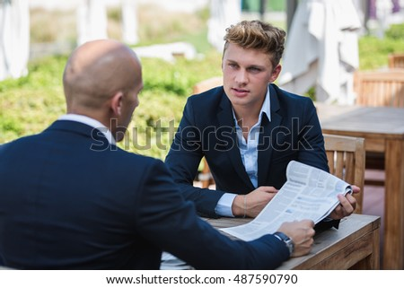 Businessman meeting outdoor. Two young guys talking in a cafe.