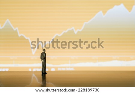 businessman miniature look at the stock chart tablet - stock photo