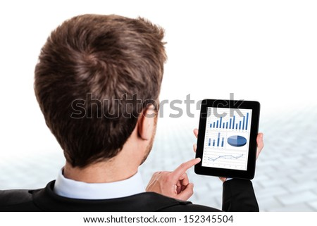 Businessman monitoring stock market graphs on his tablet - stock photo
