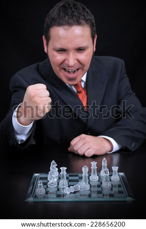 Businessman moving a chess piece to win the game on the black background