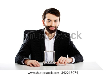 Businessman moving newton balls in office. - stock photo