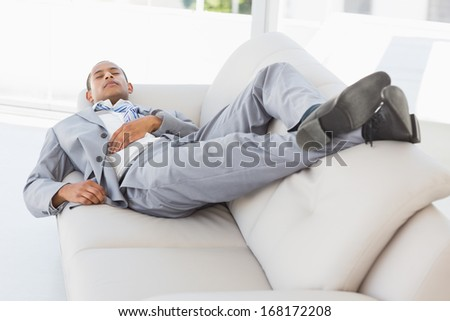 Businessman napping on the couch in the office