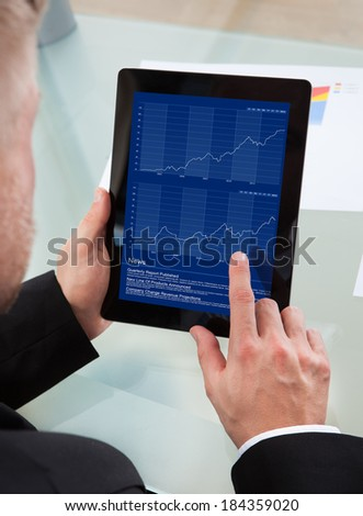 Businessman navigating on his tablet-pc using his finger on the touchscreen as he studies an online report  over the shoulder view of the screen
