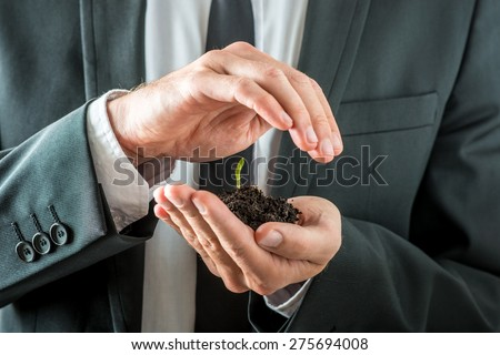 Businessman nurturing a germinating seedling in rich fertile soil cupping it in his hand while covering it with the other conceptual of awareness of conservation of the planet. - stock photo