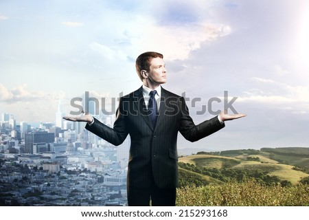 businessman offering a choice between nature and the city - stock photo