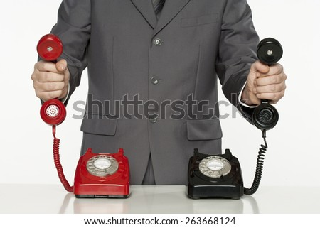 businessman offering assistance with two telephone receivers - stock photo