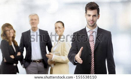 Businessman offering for handshake in office, his colleagues in the background - stock photo