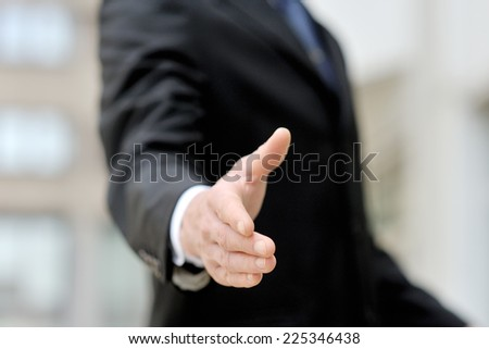 Businessman offering his hand for an handshake - stock photo