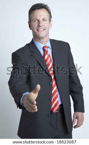 businessman offering his hand to shake - stock photo