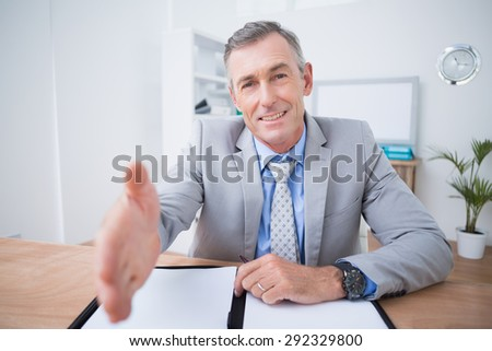 Businessman offering to shake hands in his office - stock photo