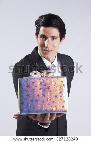 Businessman offering you a christmas gift (isolated on gray) - stock photo