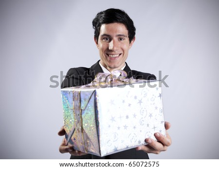 Businessman offering you a gift (isolated on gray) - stock photo