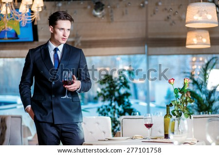 Businessman on a break. Young man businessman in formal wear standing in a restaurant while holding a glass of wine and looking forward - stock photo