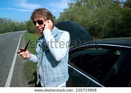 Businessman on a mobile phone in front of a broken car  - stock photo