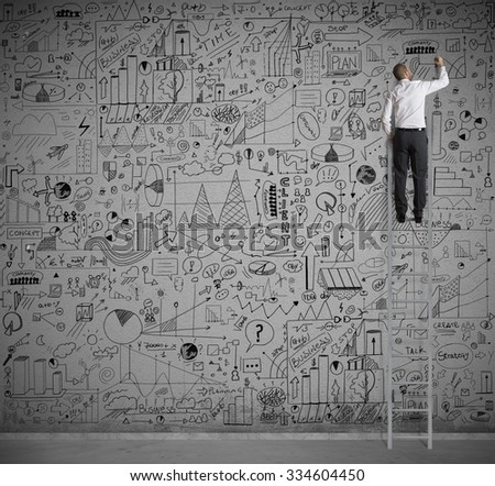 Businessman on a scale drawing on wall - stock photo