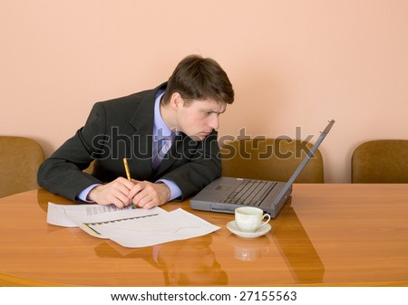 Businessman on a workplace with the laptop and a coffee cup