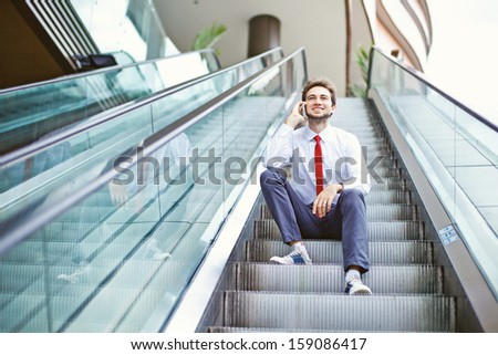 businessman on an escalator stairs talking on mobile phone