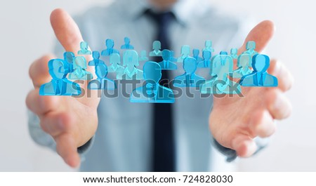 Businessman on blurred background holding 3D rendering group of blue people