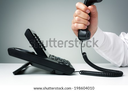 businessman on business landline telephone in an office concept for communication, contact us and customer service support - stock photo