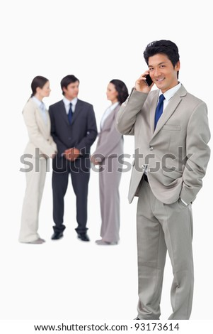 Businessman on cellphone with colleagues behind him against a white background