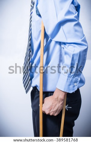 businessman on crutches, insurance concept, Disabled person in work. - stock photo