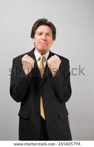 businessman on his fist isolated on gray. - stock photo