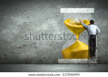 Businessman on ladder pointing at sandglass picture on wall - stock photo