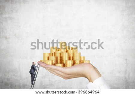 Businessman on ladder trying to reach hand with golden coins. Concrete background. Concept of career growth. - stock photo