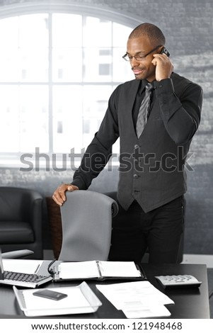 Businessman on mobile telephone call, standing at office desk, concentrating.