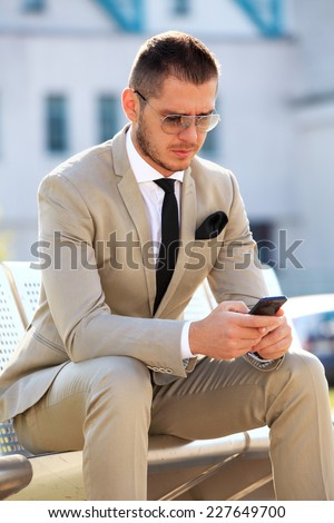 Businessman On Park Bench Using Mobile Phone in the city