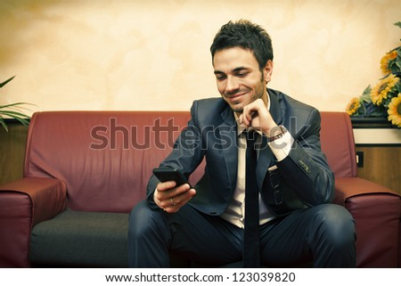 Businessman on sofa with his smart phone - stock photo